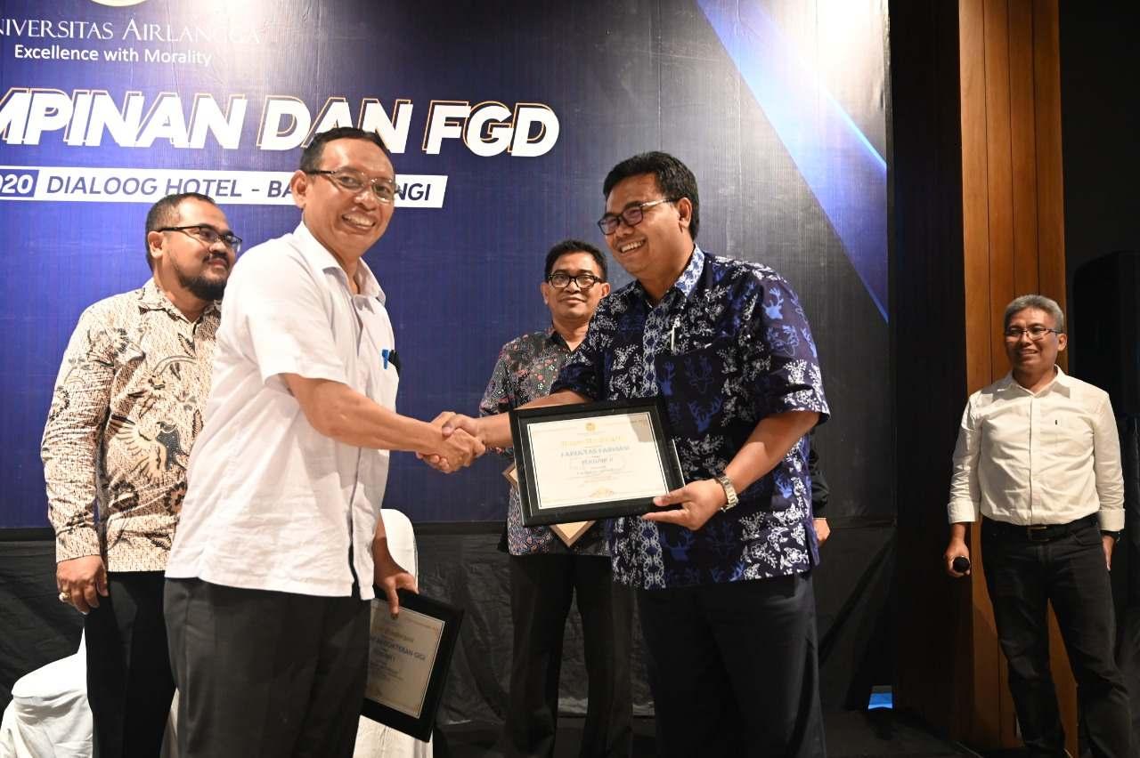 Prof. Moh Nasih SE., M.T., Ak., CMA saat memberikan penghargaan kepada wakil Dekan 2 Fakultas Farmasi Dr. Dwi Setyawan, S.Si., M.Si., Apt. di Dialoog Hotel pada Senin (27/1). (Fot: Feri Fenoria)